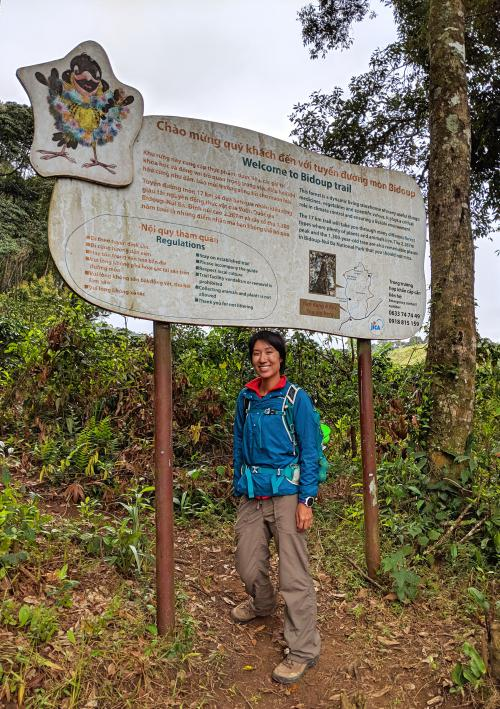 Jackie Szeto, from Life Of Doing, stands underneath the Bidoup Nui Ba National Park entrance sign.