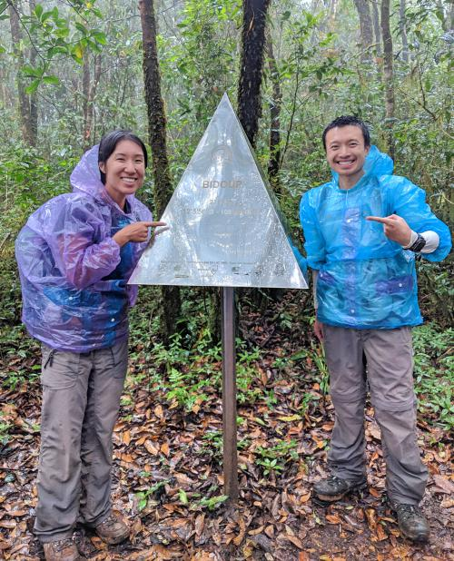 Jackie Szeto and Justin Huynh, Life Of Doing, pose with the triangle Bidoup summit sign on their Bidoup trek.