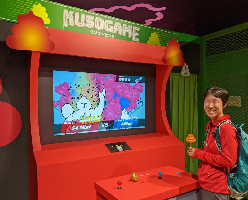 Jackie Szeto, from Life Of Doing, smiles next to a finished arcade game at the Unko Museum's Crappy Arcade area in Tokyo, Japan.