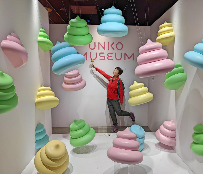 Jackie Szeto from Life Of Doing poses with the colorful poop floating from the ceiling, ground, and on the walls. This is a great spot for taking photos at the Unko Museum in Tokyo.