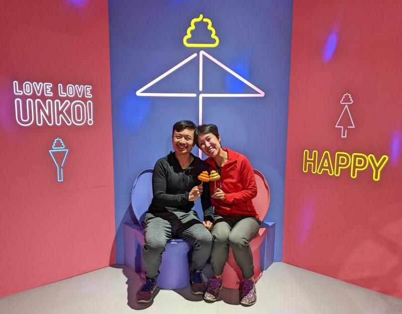 Justin Huynh and Jackie Szeto, from Life Of Doing, sit on a colorful toilet while holding their poop toy and smiling in the Unko Museum's Lover's Poop Room.