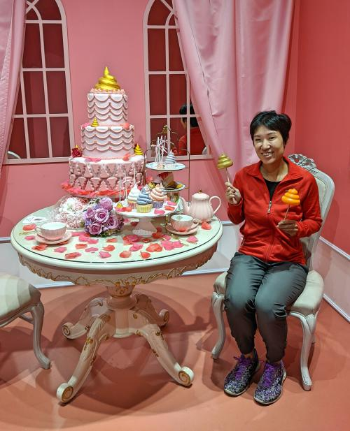 Jackie Szeto from Life Of Doing sits at a table ready for a tea party. There are tea cups, a poop-inspired three tier cake, and cupcakes.