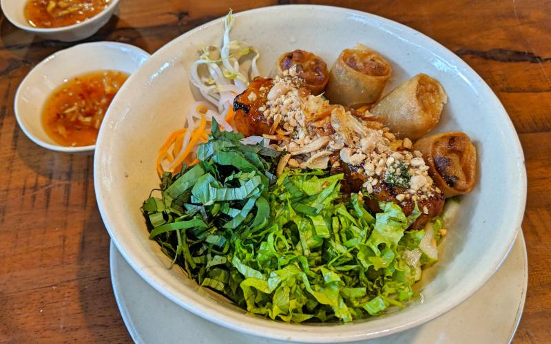 Eating delicious food is a great alternative to staying indoors during Ho Chi Minh City's rainy season. Photo is of rice noodles with lettuce, fried eggrolls, and a vegetarian tofu sausage.