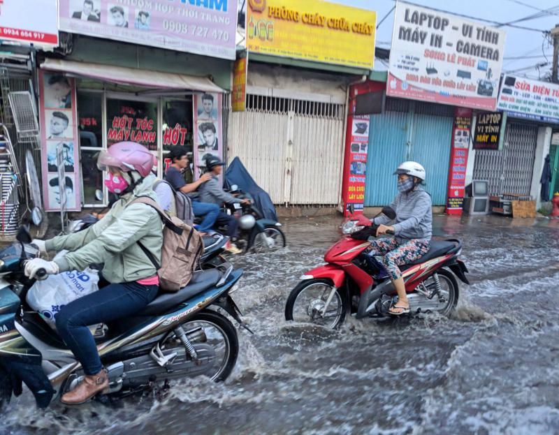 During Ho Chi Minh City's rainy season, the streets can get flooded. Life continues for the locals' even with riding a motorbike through the floods.