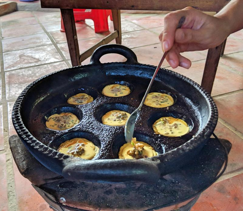 Learn how to cook your favorite Vietnamese foods on a rainy day in Ho Chi Minh City, Vietnam. Take a cooking class to sharpen your culinary skills and make local foods such as banh khot (as pictured.)