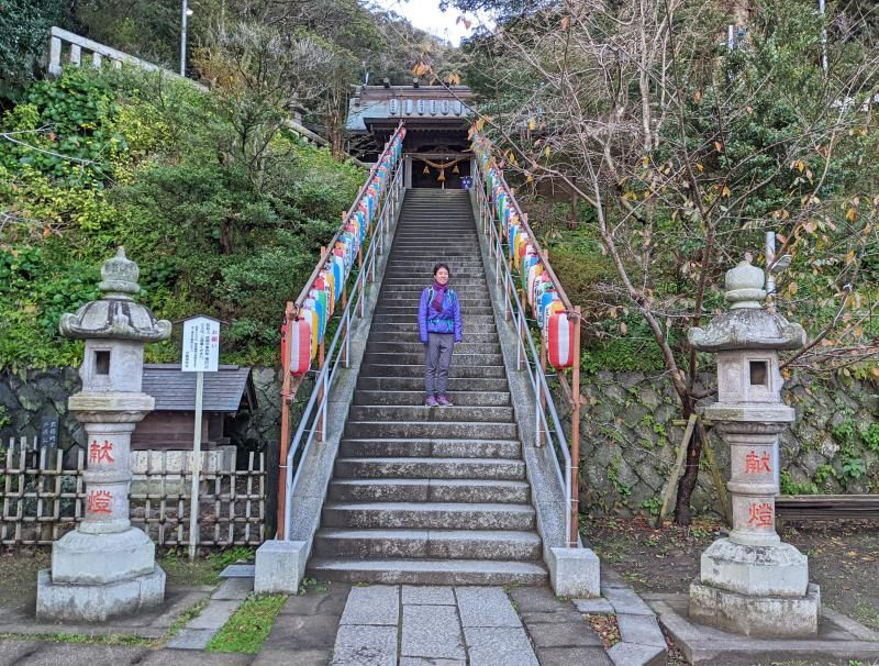 Jackie Szeto from Life Of Doing stands on the stairway of the Amanawa Shinmei Shrine in Kamakura, Japan.