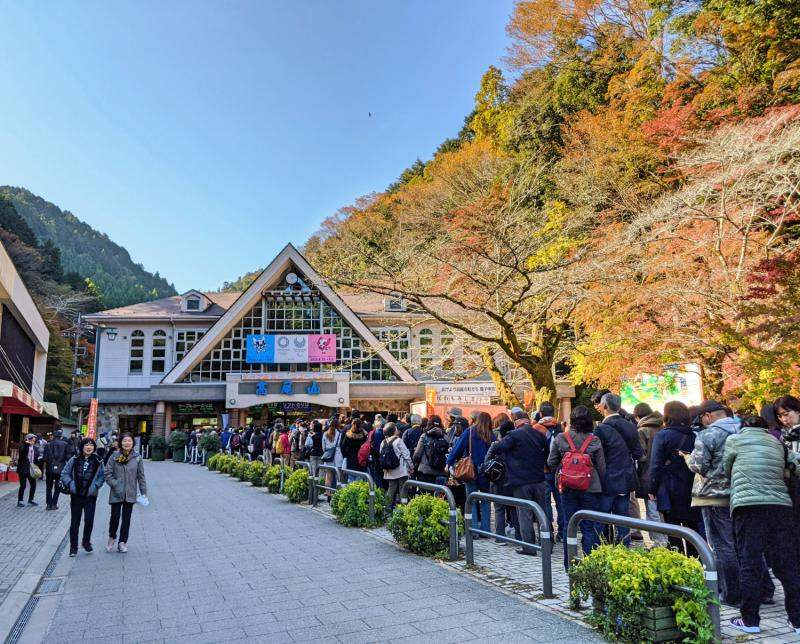 At the Mount Takao cable car station, people wait in a long line to ride either the cable car or use the chair lift to get to the Mount Takao summit.