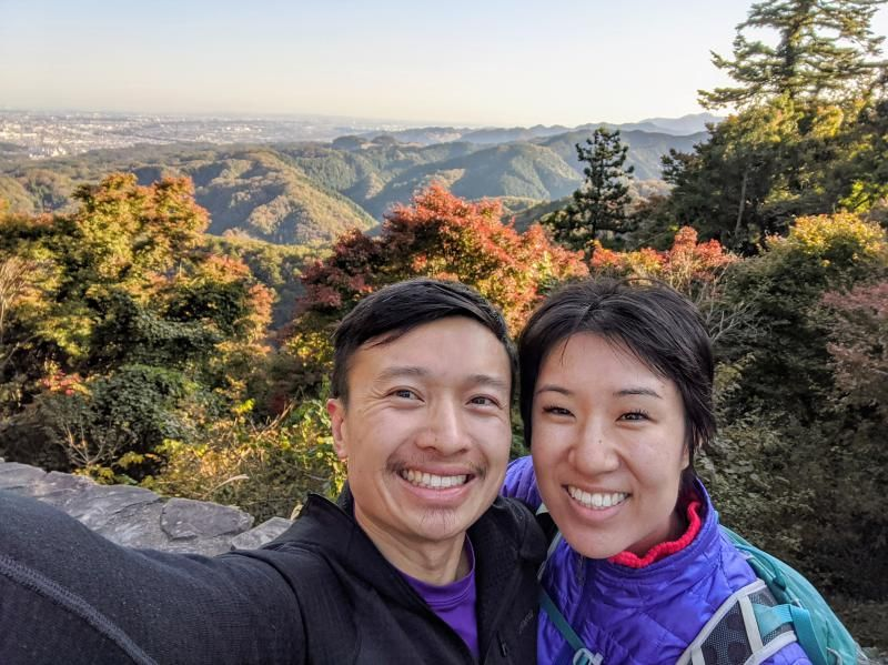 Justin and Jackie from Life Of Doing take a selfie at the Mount Takao summit. The background has the mountains and fall colored leaves.