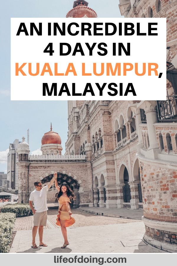 A man and woman dance in front of the Sultan Abdul Samad Building in Kuala Lumpur, Malaysia. Check out more on how to spend 4 days in Kuala Lumpur on our post.