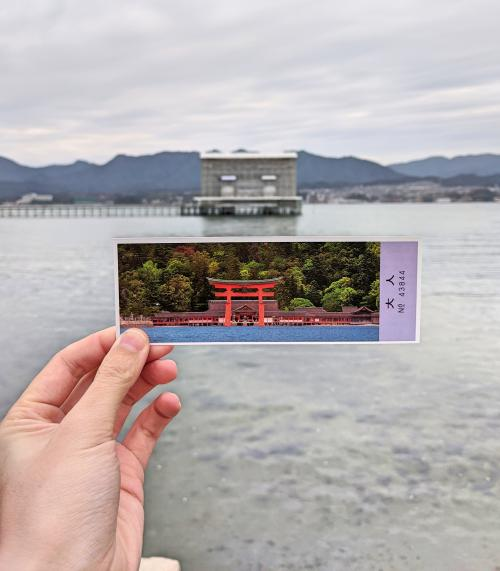 Hand holding Miyajima's Itsukushima Shrine ticket of what the floating torii gate, Otorii, is supposed to look like. However, it's in construction in the background.