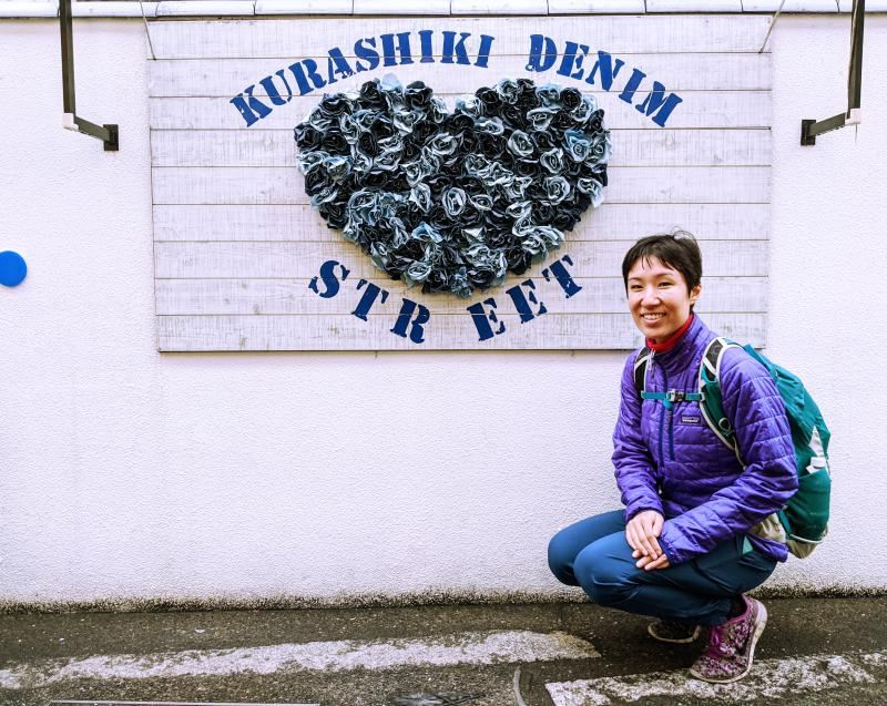 Jackie Szeto from Life Of Doing poses with the Kurashiki Denim Street artwork in Kurashiki, Japan.