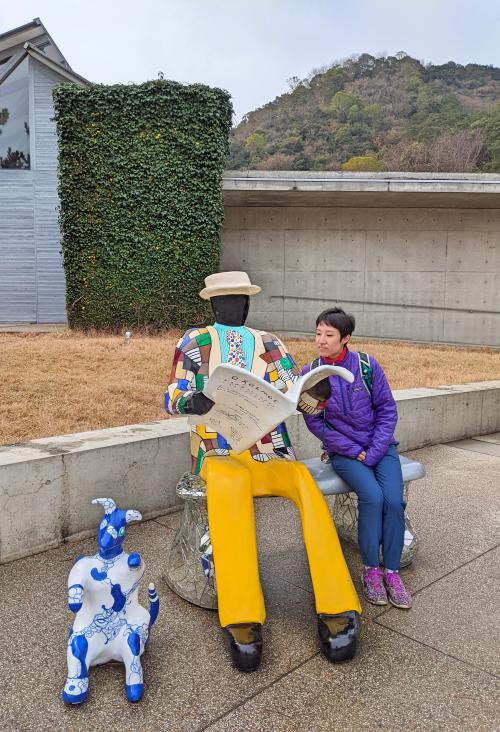 Jackie Szeto from Life Of Doing sits next to a sculpture of a man reading a magazine. The sculpture is outside of the souvenir shop of the Benesse House Hotel in Naoshima, Japan.