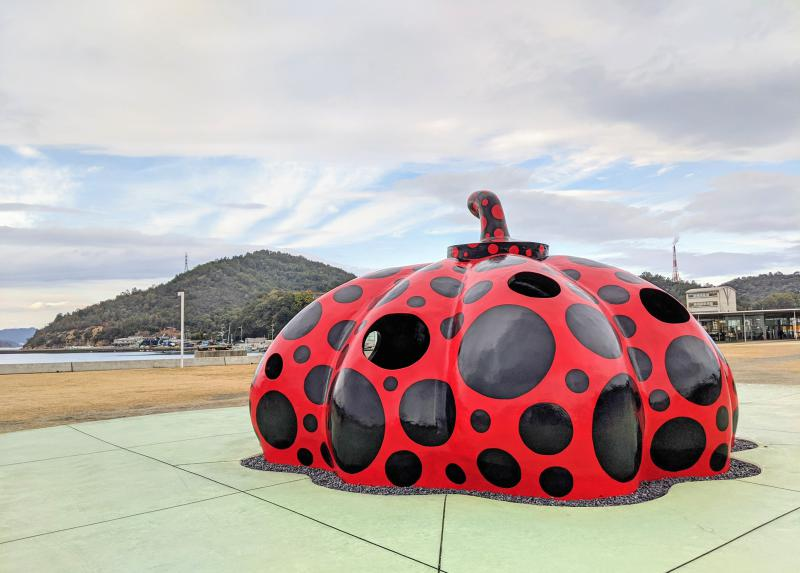 The Red Pumpkin with black dots is a famous sculpture by Yayoi Kusama and located in Naoshima, Japan. The pumpkin has holes where you can go inside to pop your head out.