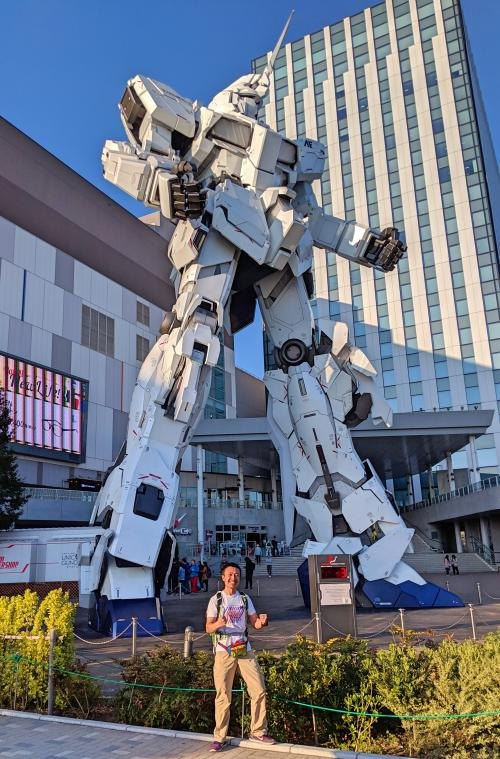 Justin from Life Of Doing poses with the life size Unicorn Gundam Statue in Odaiba, Tokyo, Japan