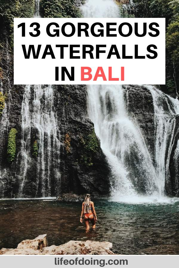 A woman in a swimsuit wades in one of the Bali waterfalls.