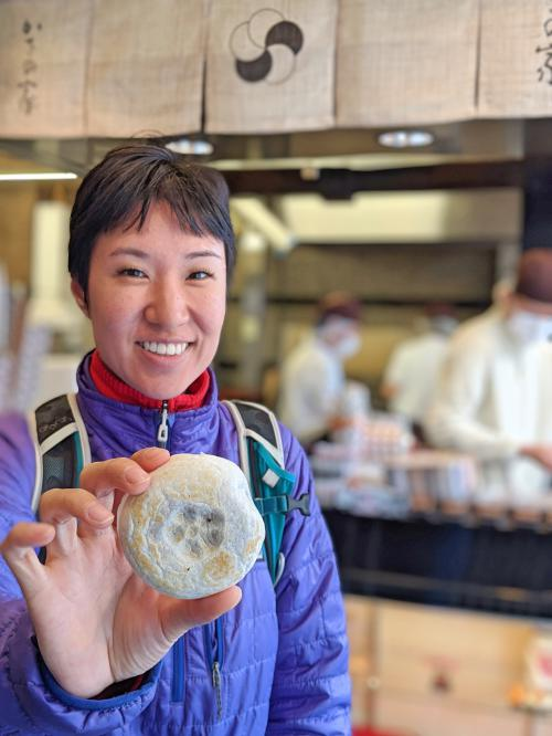 Jackie Szeto, from Life Of Doing, holds an umegae mochi, a circular rice cake filled with red beans and stamped with a plum blossom. It's a top item to try in Dazaifu, Japan.