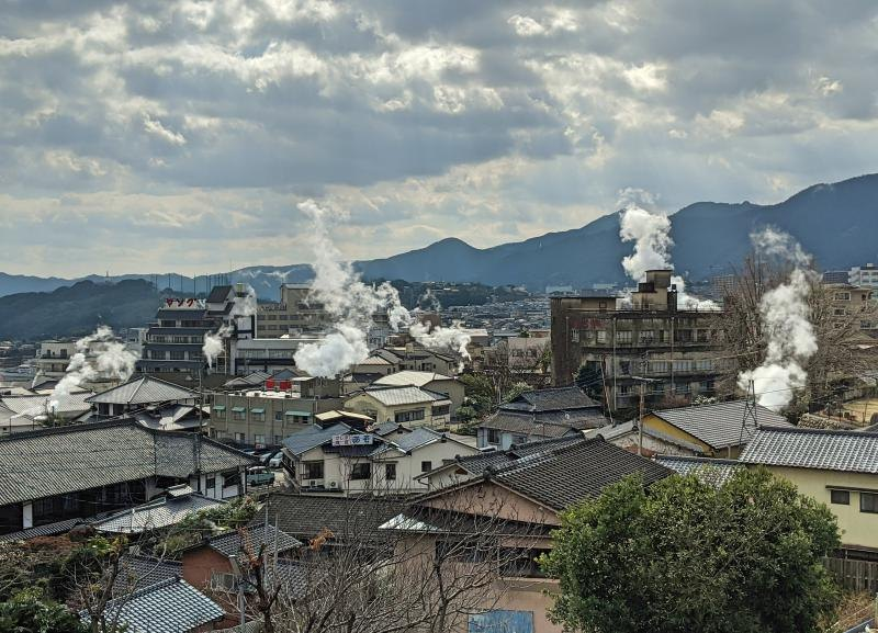 View of rooftops which has steam coming out from onsens in Beppu, Japan