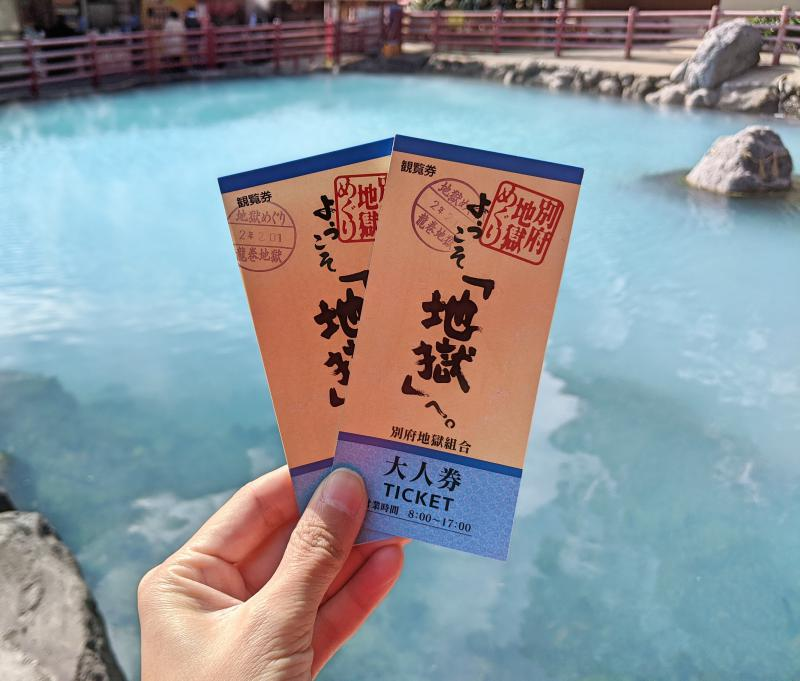 Jackie Szeto, from Life Of Doing, holds up the Seven Hells of Beppu tickets with the background of a hot spring.