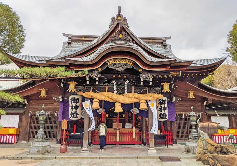 A woman prays at the Kushida Shrine in Fukuoka, Japan. It's one of the best places to visit in Fukuoka.