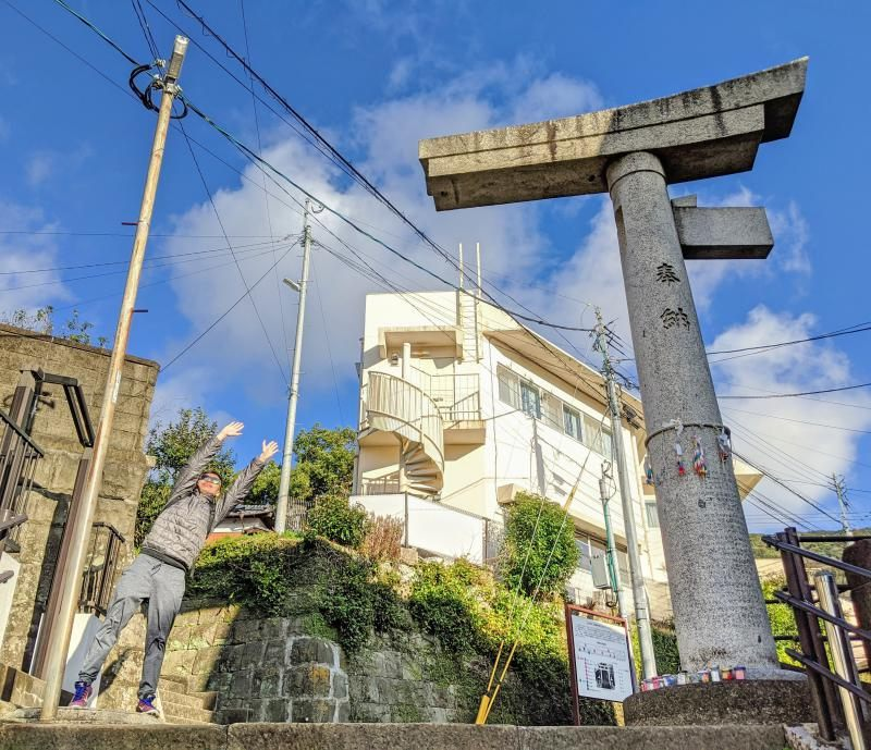 Justin Huynh, from Life of Doing, extends his arms out to pretend to be the other side of the Sanno torii gate in Nagasaki, Japan.