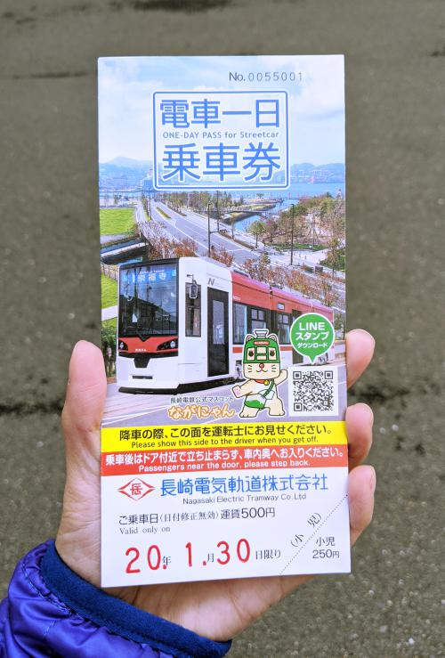 Jackie Szeto, from Life Of Doing, holds up the Nagasaki street car tickets which can be used during your one day Nagasaki itinerary.