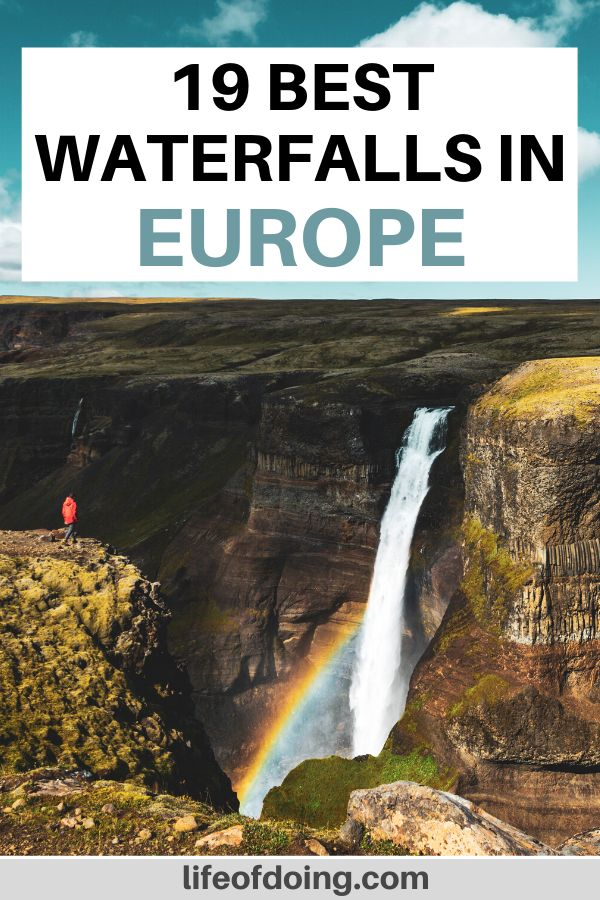 A person in a red jacket is on a cliff overlooking the stunning rainbow and waterfall in Iceland.
