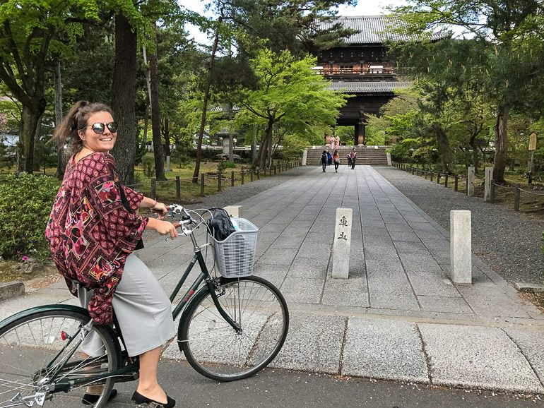 A woman smiles while riding a bicycle to Kyoto's landmarks.