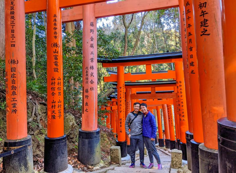Justin Huynh and Jackie Szeto, Life Of Doing, pose at the Fushimi Inari Taisha Shrine in Kyoto, Japan. It's the best place to visit during your 5 days in Kyoto.