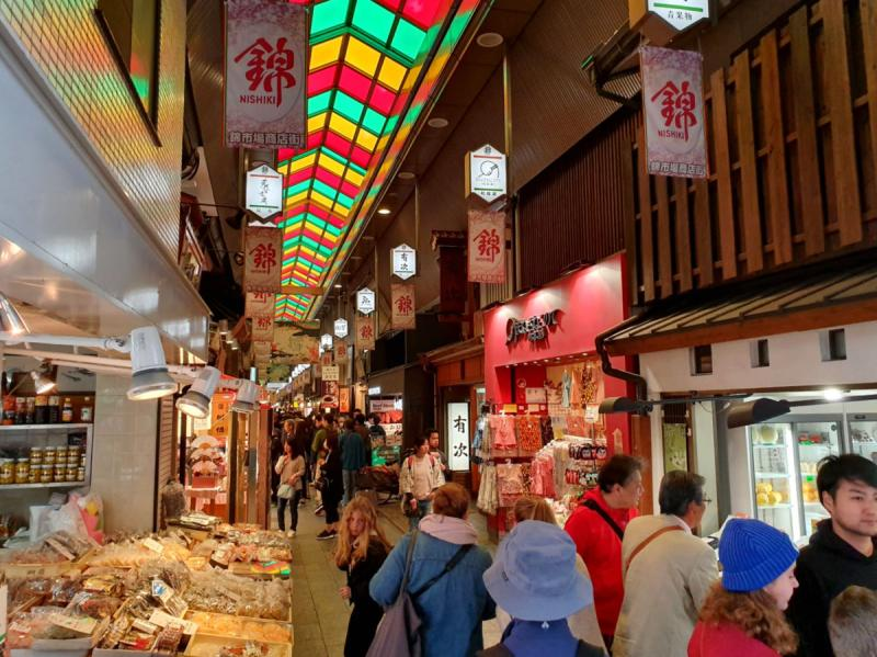 Visitors browse through the foods and snacks at Nishiki Market in Kyoto, Japan.
