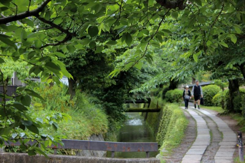 Two people walk along Kyoto's Philosopher's Pass, which is next to a canal.