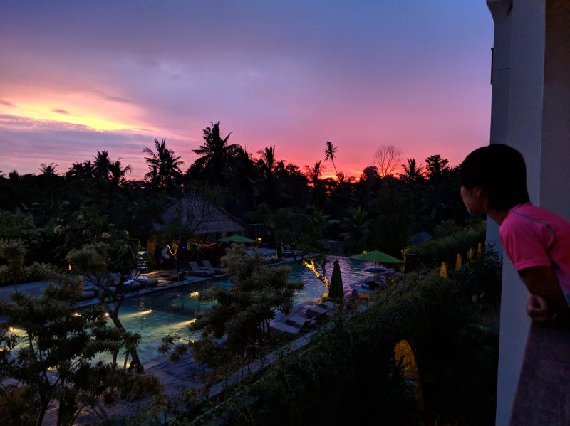 Jackie Szeto, Life Of Doing, peers from the balcony to see the sunset in Bali, Indonesia. The skies are pinks, purples, and orange.