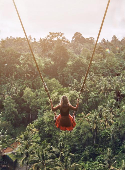 A blonde woman in a red dress is on one of the Bali swings and has a jungle view.