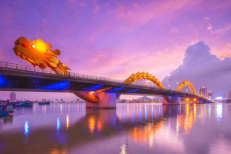 The Dragon Bridge in Danang, Vietnam glows a bright yellow and different colors and has a purple and pink skies during sunset.