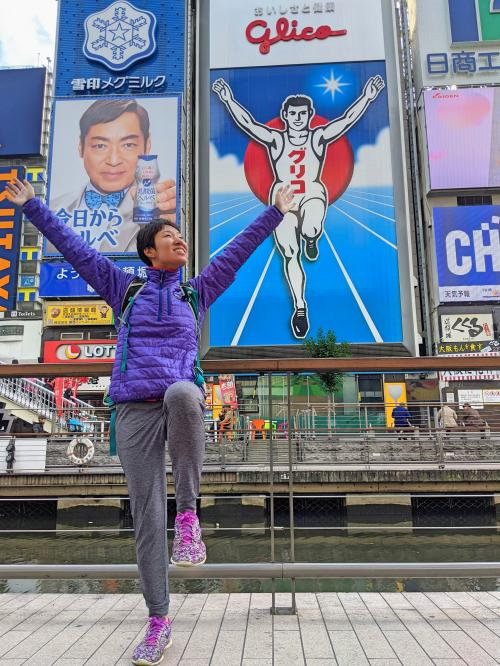 Jackie Szeto, Life Of Doing, poses with her arms up just like the Glico Man sign in Dotonbori Street, Osaka, Japan.