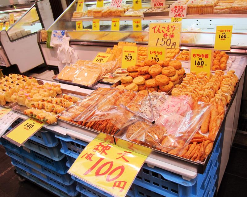 Kuromon Market in Osaka, Japan has a variety of food items to try such as fish cakes, sushi, and more.