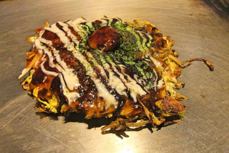 Okonomiyaki cooked on top of a grill at Osaka's Tako Hachi Sohonten