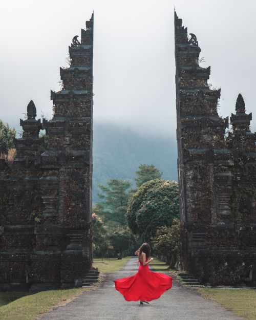 Woman in a red dress twirls in front of the Handara Gate in Bali, Indonesia