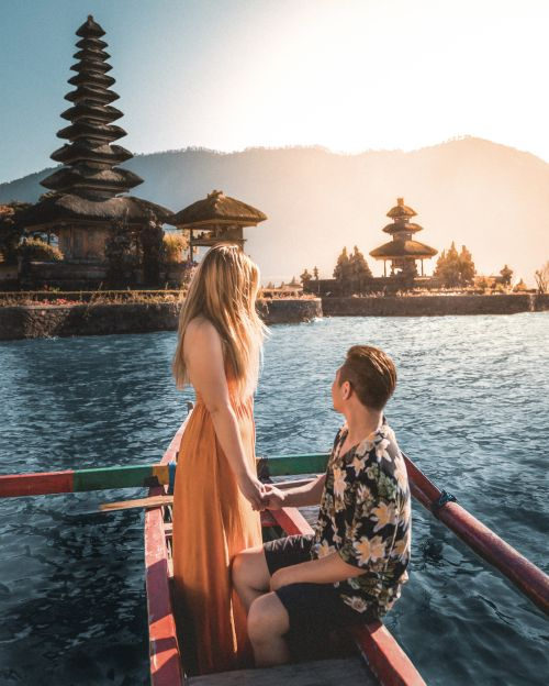 A woman and man ride a wooden boat while overlooking the Pura Ulun Danu Beratan in Bali, Indonesia