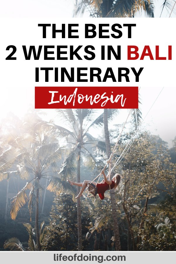 A woman in a red dress is on a Bali swing with palm trees and rice terraces in the backdrop. You'll need at least 2 weeks in Bali to explore the island.