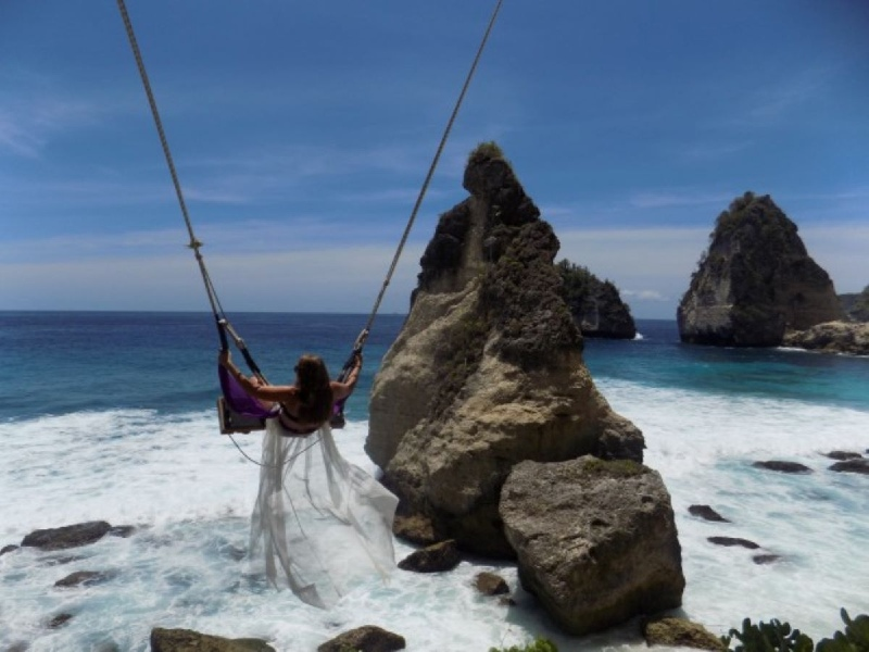Woman on a swing at Diamond Beach, Nusa Penida