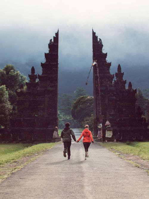 A man and woman run towards the entrance of the Handara Gate in Bali