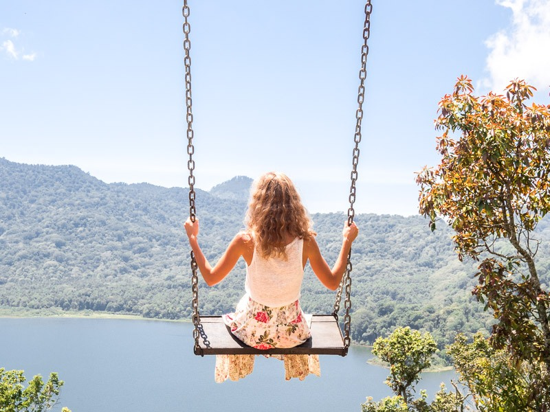 A woman wearing a flower skirt is on a swing that overlooks Lake Danau Buyan at Hidden Hills Wanagiri in Bali, Indonesia