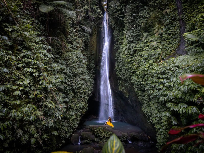 A woman in a yellow dress sits at the base of the Leke Leke Waterfall in Bali, Indonesia