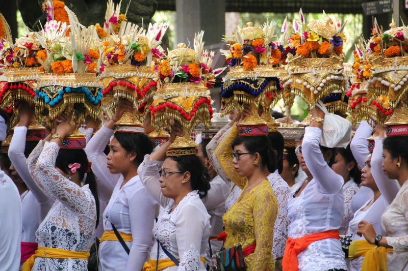 Indonesian women hold offerings on top of their heads as they participate in a Bali procession.