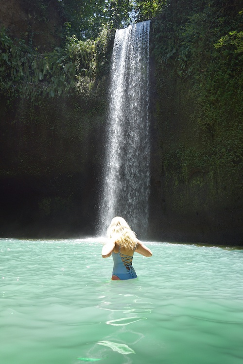 A woman is in front of the Tibumana Waterfall in Bali, Indonesia