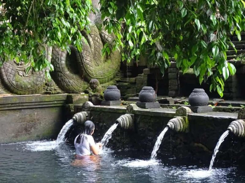 A woman performs the purification ritual at the Tirta Empul Temple fountains.