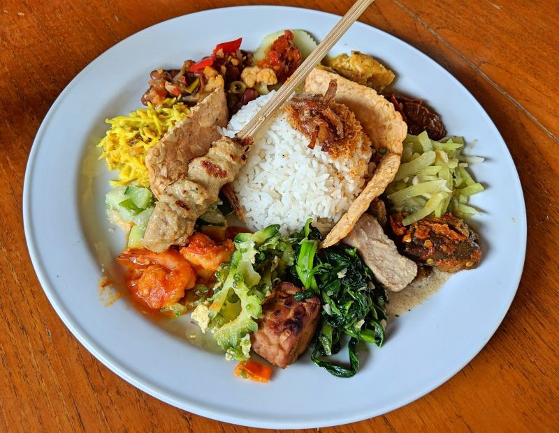 A plate of nasi campur, Indonesian cuisine, that has rice, vegetables, chicken skewer, tempeh, meat, and tempeh.