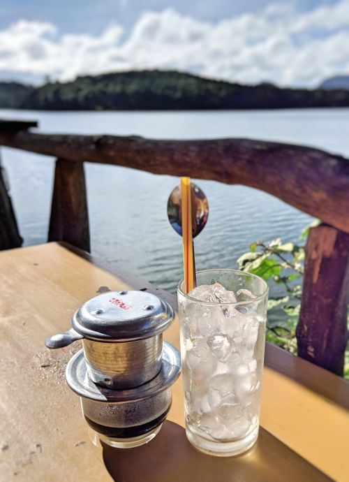 In Dalat, Vietnam, enjoy iced Vietnamese coffee in a coffee phin with a lake in the background.