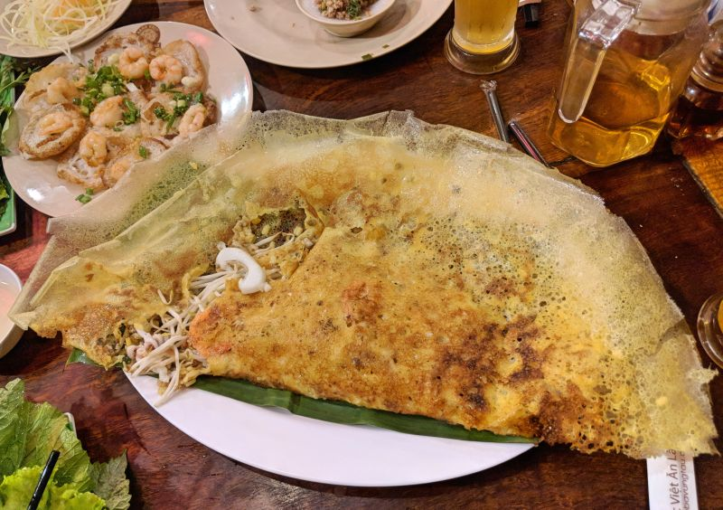 A plate of Vietnamese pancake (banh xeo) stuffed with bean sprouts and seafood and a side order of rice cakes (banh khot)