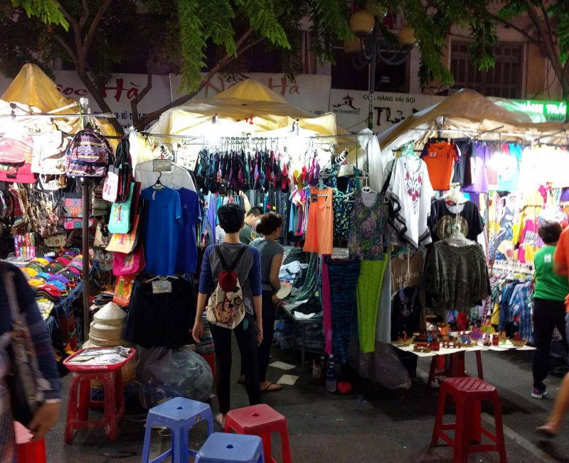 Visitors stop a stall selling clothing at the outdoor Ben Thanh night market in Ho Chi Minh City, Vietnam